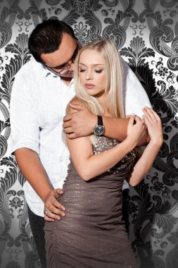 Handsome man hugging blond girl from back