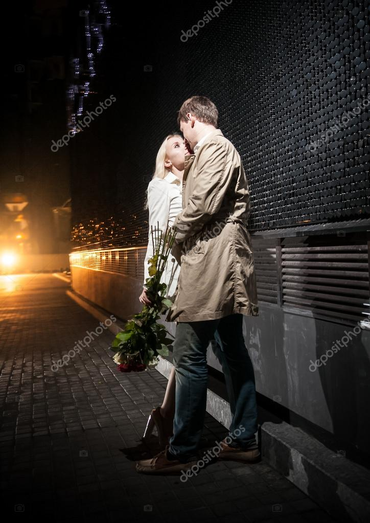 couple in love hugging on street at night