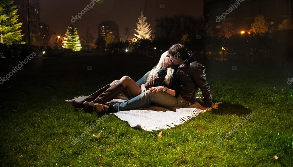 Night shot of couple in lying on grass