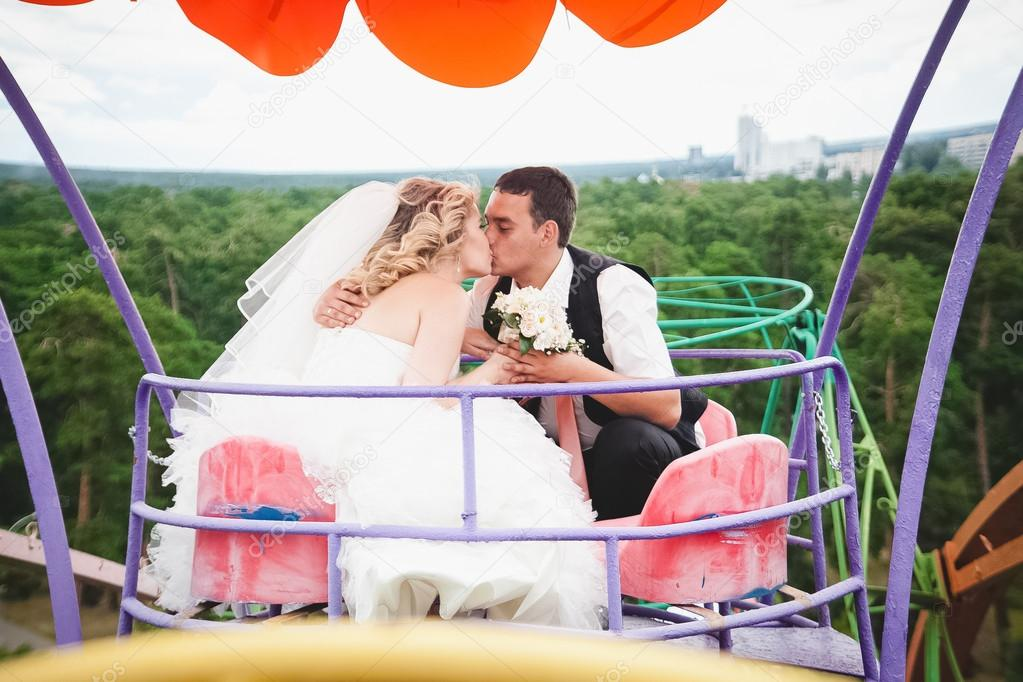 Married couple riding on Ferris wheel and kissing