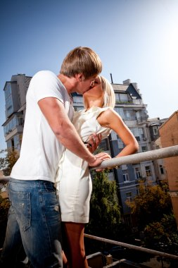 Young couple kissing on fire exit stairs against city view