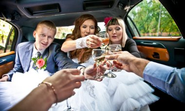 married couple clinking glasses with friends in car