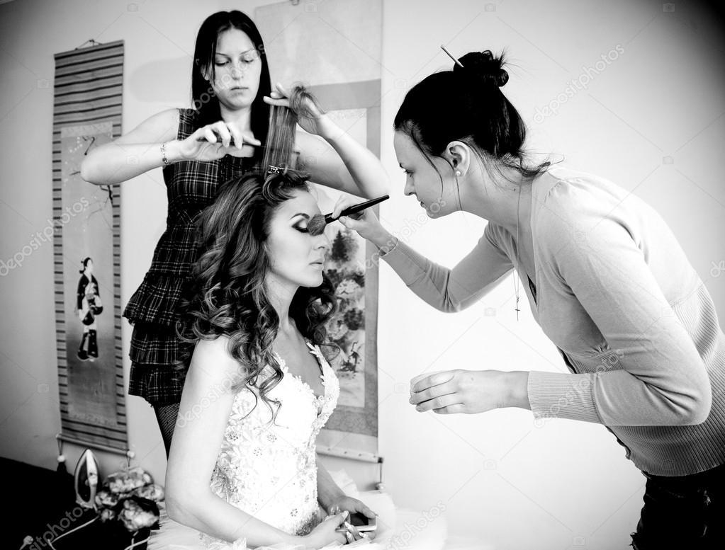 Makeup artist and hairdresser preparing bride for wedding