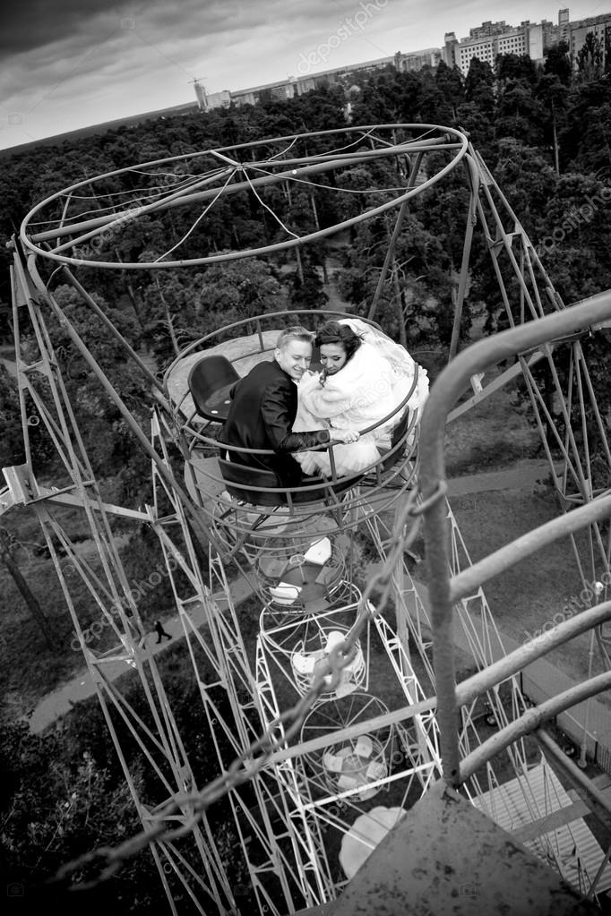 Portrait of newly married couple riding in ferris wheel