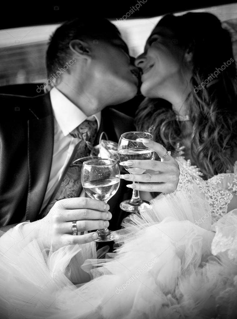 Married couple kissing in car while holding glasses of champagne