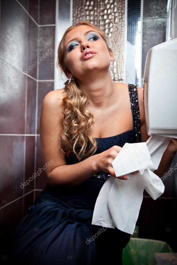 Sexy blond woman tearing off toilet paper at lavatory