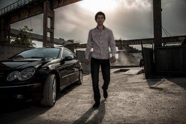 Man walking near black luxury car against industrial background