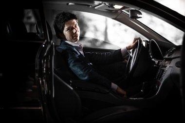 Portrait through open door of driver holding steering wheel