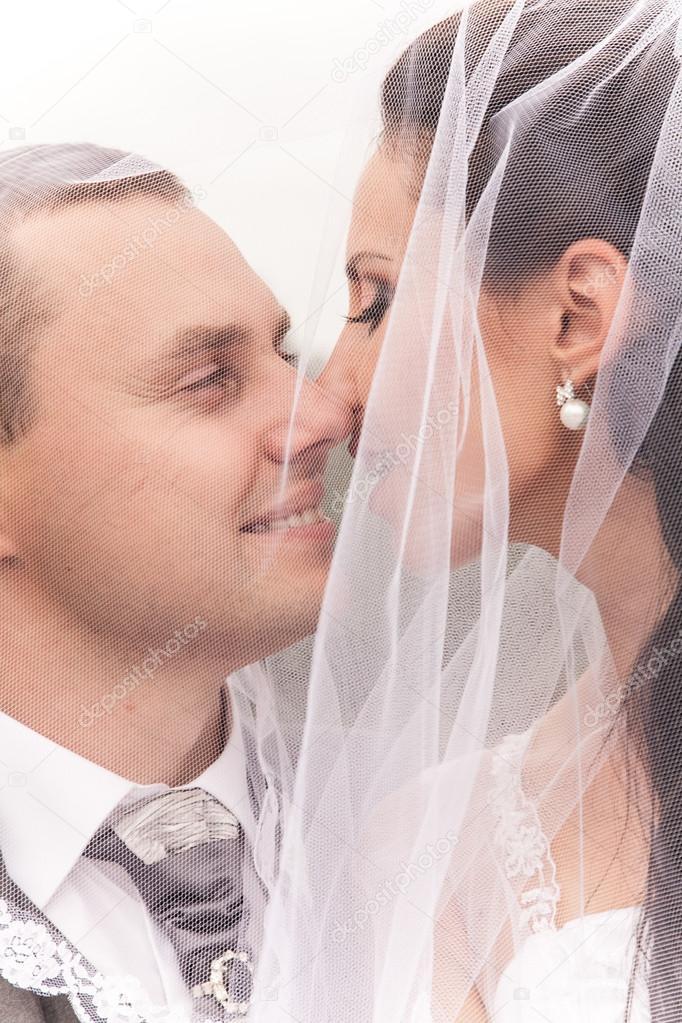 7716d892df6 Coppia di sposi cerca a vicenda sotto il velo da sposa — Foto di Kryzhov