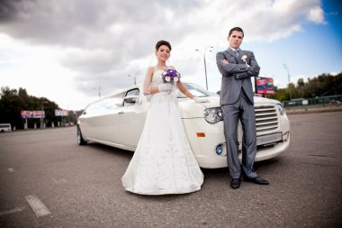 Just married couple standing against long white limousine