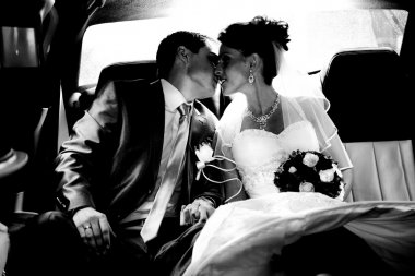 Portrait of just married couple kissing in car
