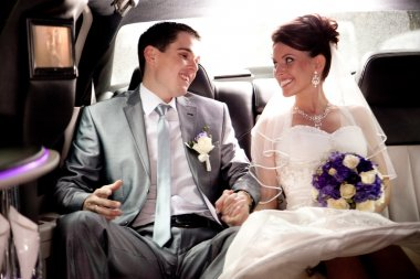 Bride and groom looking at each other on backseat of car