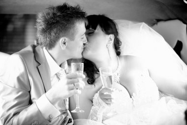 Newly married couple holding glasses and kissing at car