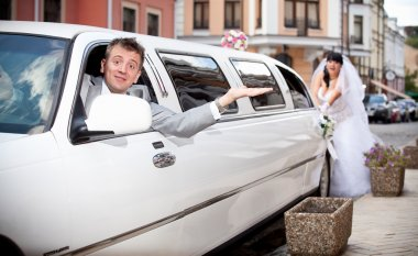 Groom sitting in car while bride pushing it
