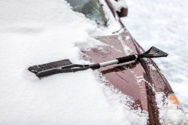 Black brush lying on car covered in snow