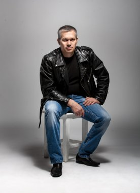 Adult man in leather jacket sitting on white chair