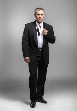 Portrait of elegant man in black suit with untied bow tie