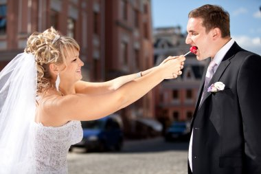 Greedy bride taking lollipop from groom while he was eating it