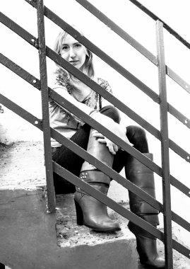 Portrait of teen girl sitting on stairs behind metal railings