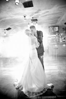 Bride and groom kissing passionately during first dance