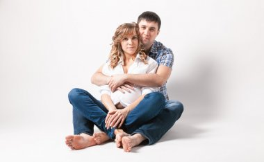 Man hugging pregnant wife sitting on floor