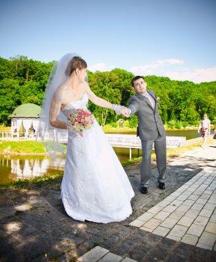 Outdoor portrait of bride pulling by hand resist groom