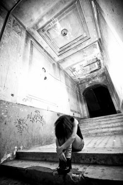 Depressed lonely woman sitting on stairs at abandoned building