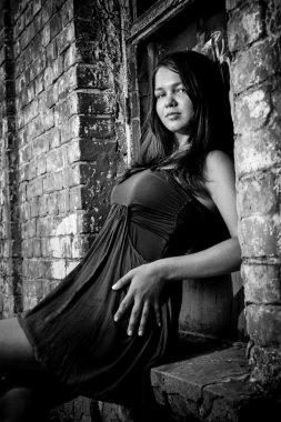 Brunette woman in short dress leaning against old brick wall