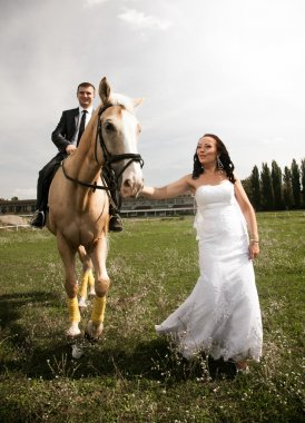 Photo of bride pulling horse by rein with groom riding in saddle