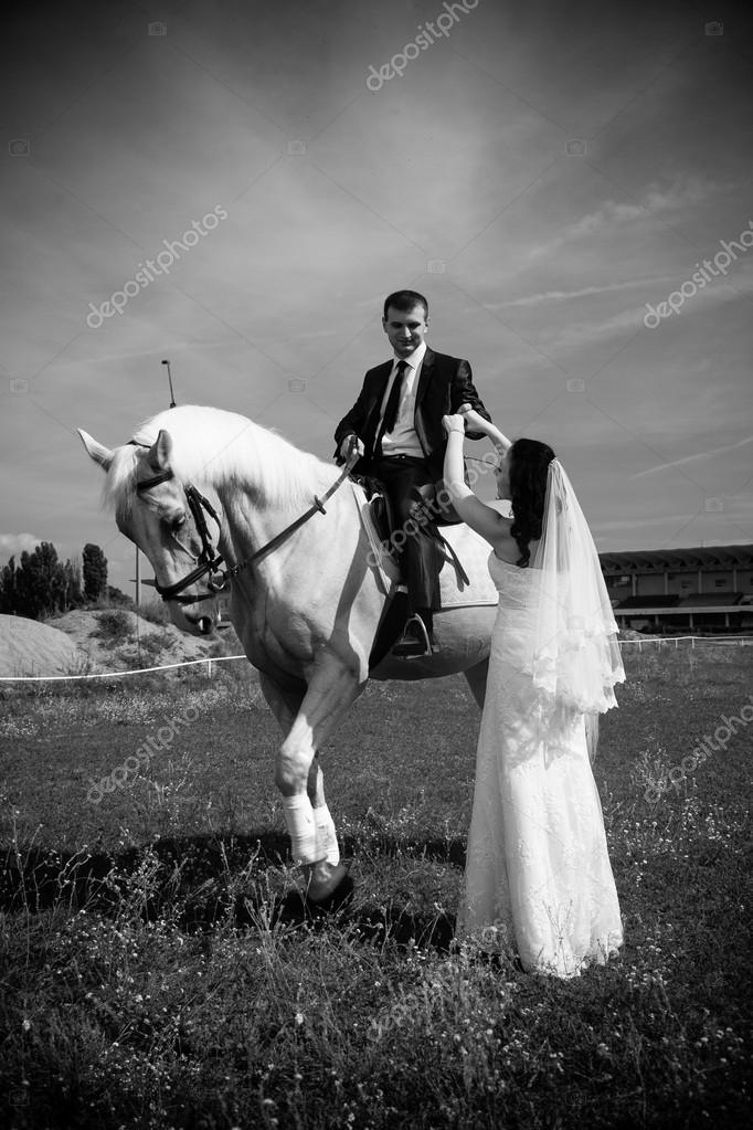 Photo of bride and groom on horse at meadow