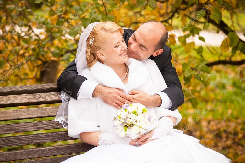 Middle aged groom kissing bride sitting on bench