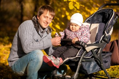 Father and daughter in buggy at autumn park