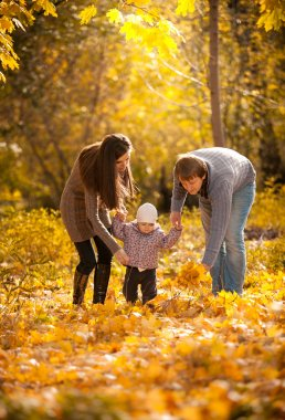 Parents teaching small daughter to walk at autumn park