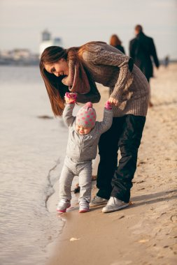 Little girl making first steps on beach with help