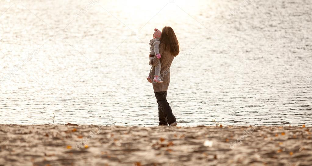 Mother holding daughter on hands and looking at sea
