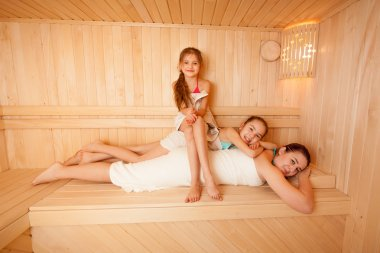 Two daughters lying on mothers back at sauna