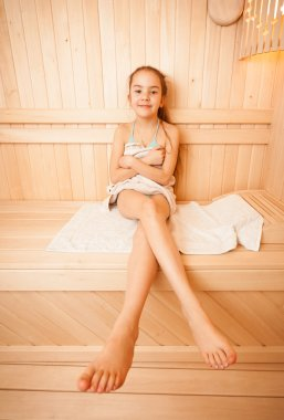 Girl with long legs sitting on towel at sauna