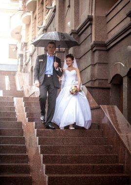 Married couple walking under umbrella on stairway