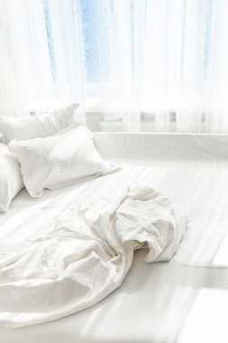 Photo of unmade bed against window