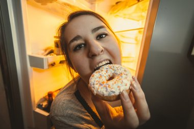 Hungry woman eating donut on kitchen
