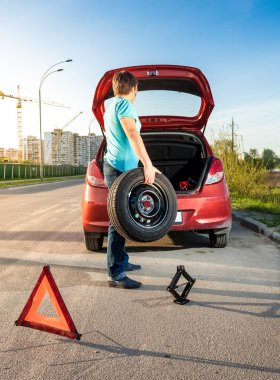 man taking spare wheel out of trunk