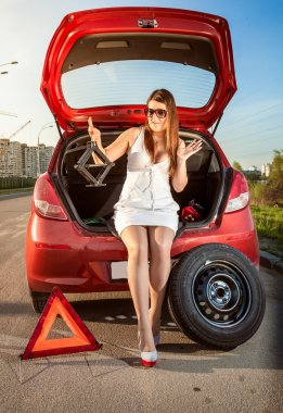 Woman looking on jack screw near car with punctured wheel