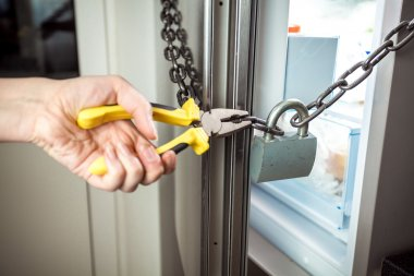 photo of woman cutting chain on fridge with pliers