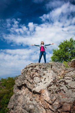beautiful woman standing on top of high cliff with stretched out
