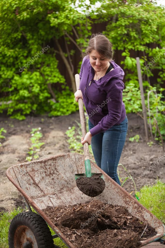woman fertilizing garden bed with compost from wheelbarrow