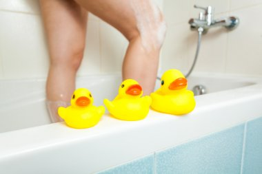 three rubber ducks at bathroom with woman having shower