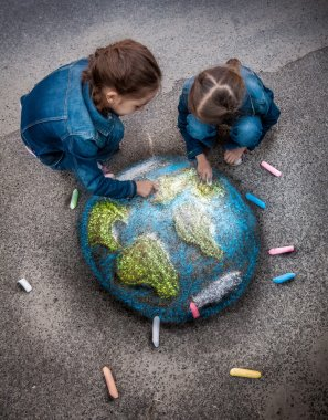 two girls drawing realistic Earth image with chalks on ground