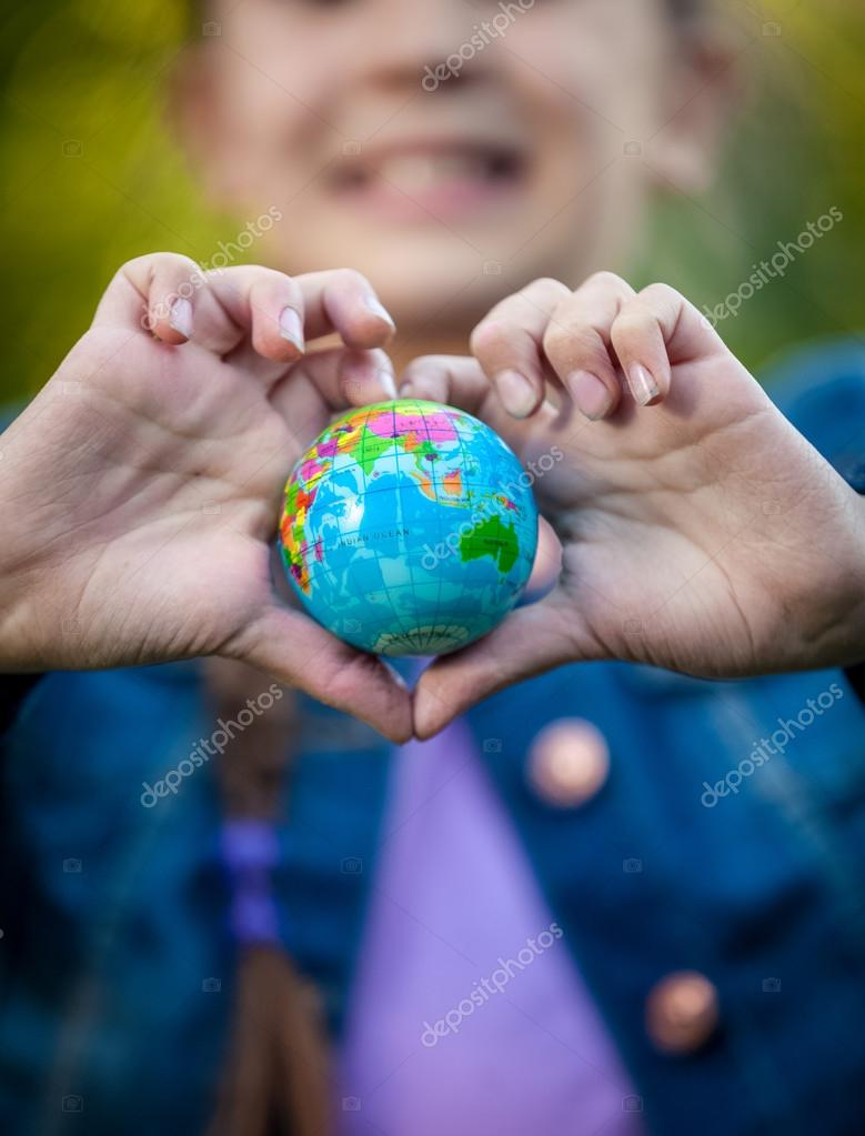 smiling girl holding globe in hands folded in shape of heart