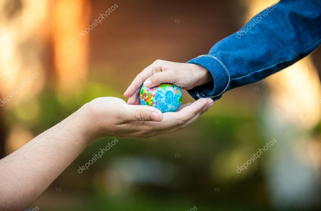 men hand and little girl hands holding planet Earth
