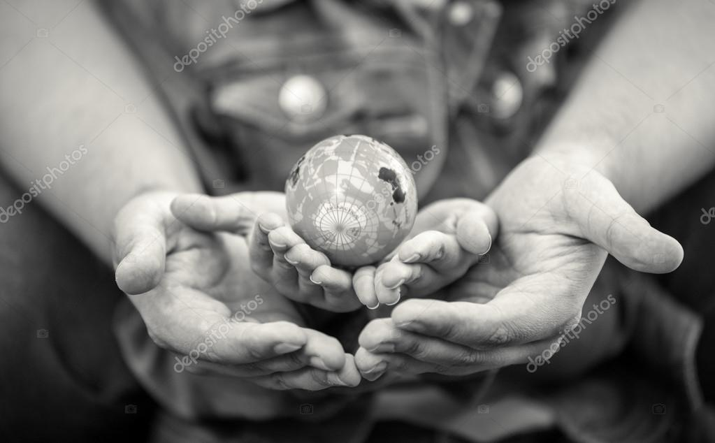 Shot of man protecting girls hands holding globe